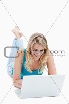 A smiling woman with a laptop is lying on the ground with her le
