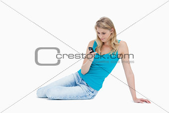 A woman sitting on the floor looking at her mobile phone