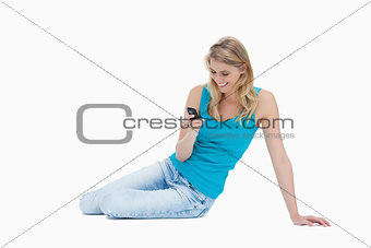 A smiling woman is sitting on the floor holding her mobile phone