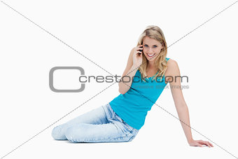A smiling woman is sitting on the floor talking on her mobile ph