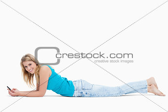 A smiling woman holding a mobile phone is lying on the floor