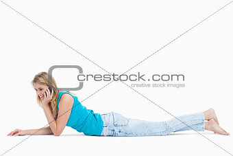 A happy woman lying on the floor is talking on her mobile phone