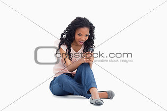 A surprised woman is sitting on her floor looking at her mobile