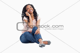 A smiling woman talking on her mobile phone is looking up