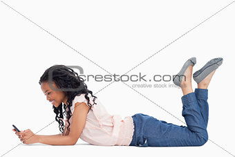 A young woman lying on the ground is texting off her mobile phon