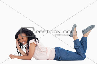 A smiling woman is lying on the floor talking on her mobile phon