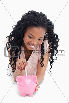 A young girl lying on the floor putting money into a piggy bank