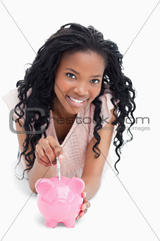 A young girl looking at the camera is putting money into a piggy