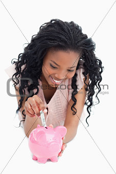 A young woman lying on the floor is putting money into a piggy b