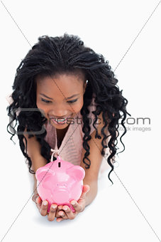 A smiling woman is looking at a piggy bank she is holding