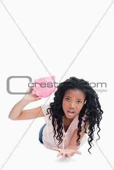 A worried young woman holding an empty piggy bank