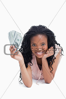A woman resting her head on her hand is holding Americn dollars