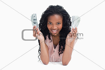 A young woman is holding American dollars and smiling at the cam