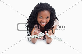 A young woman lying on the floor is holding American dollars out