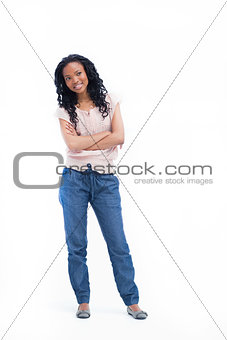 A young woman standing with her arms folded is smiling