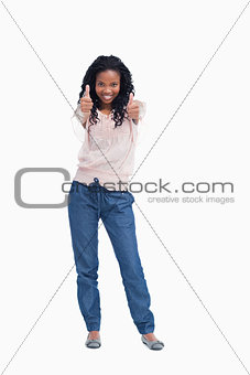 A young woman standing with her thumbs up