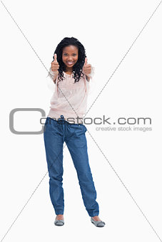 A smiling woman is standing with her thumbs up