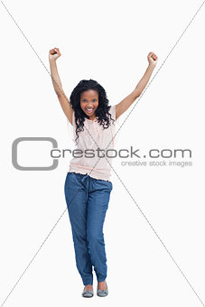 A young happy woman stands with her hands in the air