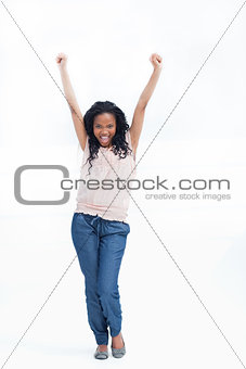 A young laughing woman stands with her arms held up in the air
