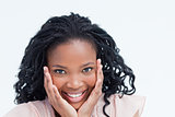 Head shot of a smiling young woman holding her head in her hands