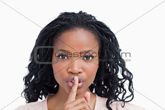 A young woman with her finger up to her lips