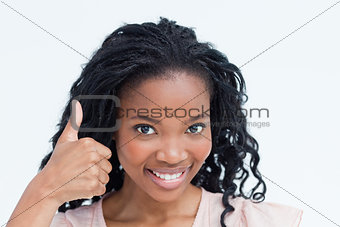 A young woman smiling at the camera with her thumb up