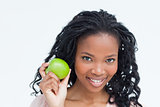 A smiling young woman holding an apple up longside her face
