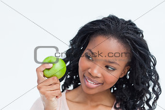 A woman is looking at an apple she is holding