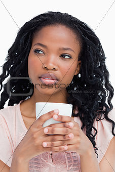 A young woman holding a cup with her both hands