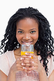 A young woman holding a glass of orange juice with her both hand