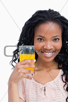 Close up of a smiling young woman holding a glass on orange juic