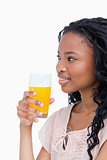 A side shot of a girl holding a glass of orange juice