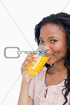 A girl looking at the camera is drinking orange juice
