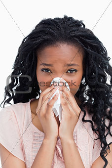 A young woman is blowing her nose in a tissue