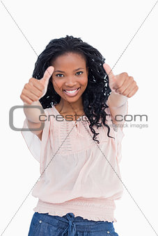 A woman is smiling and has her both thumbs up