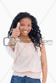 A girl is smiling and giving a thumb up