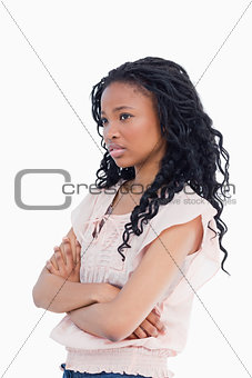 A worried looking girl with her arms folded