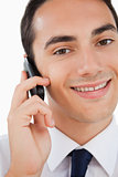 Close-up of a smiling man in a suit calling with his cellphone