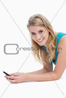 A woman holding a mobile phone is smiling at the camera