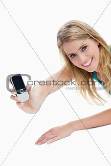 A young woman holding out her mobile phone is looking at the cam