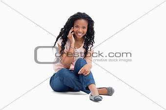 A woman smiling at the camera sitting on the floor is talking on