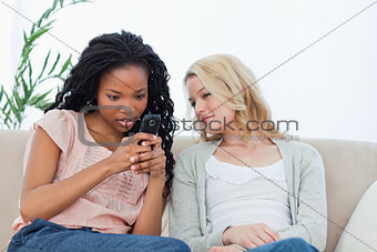 A woman is texting on her mobile phone while her friend watches