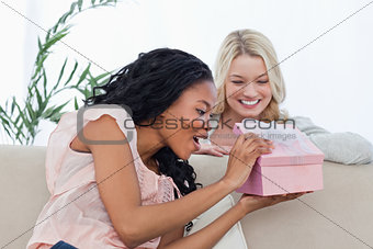 A surprised woman looking in a box given to her from a friend