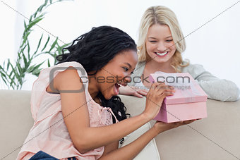 A delighted woman looks at a present given to her by a friend