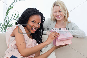 A woman holding a pink box smiles at the camera with her friend
