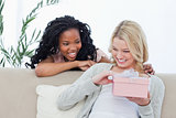 A smiling woman is holding a pink box and her friend is behind h