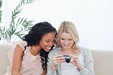 Two women look at photos on a digital camera