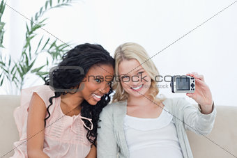 A woman takes a photo of herself and her friend on a digital cam