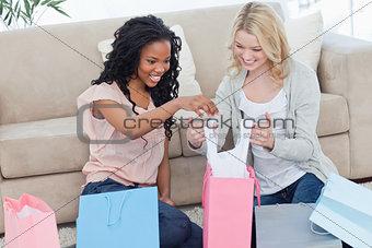Two women look through shopping bags