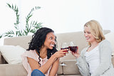 Two women smiling at each other are holding wine glasses